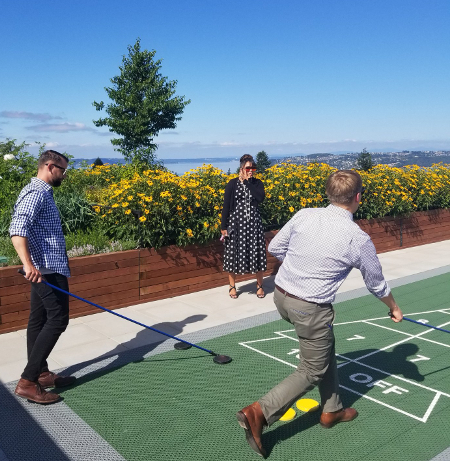 Members play shuffleboard on Proctor Station's rooftop deck